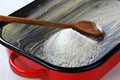 Greased baking tin with desiccated coconut heap of in pan Stock Images
