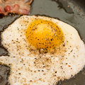 Greasy fried egg and bacon a breakfast of an frying in a frying pan Stock Photo