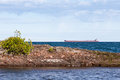 Great Lakes Freighter Passing Behind a Rocky Island Royalty Free Stock Photo