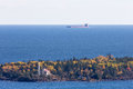 Great Lakes Oar Boat Passing Behind a Lighthouse Royalty Free Stock Photo