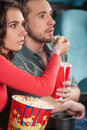 Great movie close up of young couple feeding each other while watching at the cinema Royalty Free Stock Photos