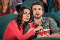 Great movie young couple eating popcorn and drinking soda while watching at the cinema Royalty Free Stock Images