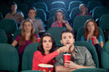 Great movie young couple feeding each other while watching at the cinema Stock Photography
