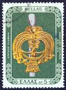 GREECE - CIRCA 1976: A stamp printed in Greece shows a gold goddess head from a silver pin, circa 1976. Royalty Free Stock Photo