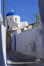 Greece cobbled street in with white washed walls leading to a church with a blue dome bearing a christian cross of the greek Royalty Free Stock Images