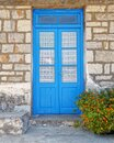 Greece, blue door on traditional island house stone wall and marigold flower Royalty Free Stock Photo