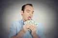 Greedy banker ceo boss corporate employee obsessed with money closeup portrait crazy guy funny looking man licking cash dollars Royalty Free Stock Image