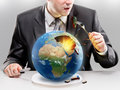 Greedy businessman eating planet earth concept Royalty Free Stock Photos