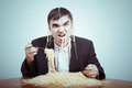Greedy consumerism concept nasty businessman eating pasta on the table Stock Photography