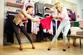 Greedy girls image of two fighting for red tanktop in department store Royalty Free Stock Images