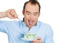Greedy man ceo closeup portrait of evil young in blue shirt eating green cash dollars from plate isolated on white background Royalty Free Stock Image