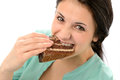 Greedy young woman eating tasty cake looking at camera Royalty Free Stock Photo