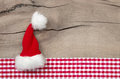 Greeeting card with santa hat for chrismas card or coupon top view of on wooden background christmas a red checked frame in Royalty Free Stock Photography