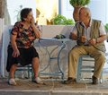 Greek couple in tavern senior sitting at table typical deep conversation waiting for their drinks to be served Royalty Free Stock Photo