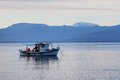 Greek fishing boat retrieving net small wooden caique clinker gulf of corinth greece snow on peloponnese mountains Stock Photo