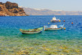 Greek fishing boats at aquamarine transparent sea thirassia near santorini island greece Stock Photo
