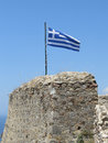 Greek flag in the background of pure blue sky and sea. Royalty Free Stock Photo
