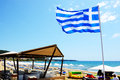 The greek flag on the beach and tourists enjoying their vacation patronikoleika greece june june in patronikoleika greece up to Royalty Free Stock Photography