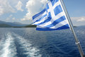 Greek flag and blue sea. Royalty Free Stock Photo