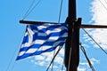 Greek flag on a ship which sails near greek coast of aegean sea Royalty Free Stock Photo