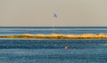 Greek flag on small piece of land in the sea Royalty Free Stock Photo