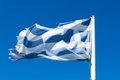 Greek flag torn with the blue sky in the background Stock Image
