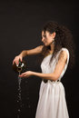 Greek girl with jug curly in a toga pouring water from a Stock Photos