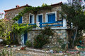 Greek house traditionaly made of stone with blue and white colored windows in Sithonia Royalty Free Stock Photo