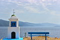 Greek little church next to a bench overlooking a calm sea view Stock Image