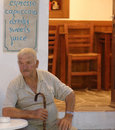 Greek man at tavern old sitting a table in folegandros greece Royalty Free Stock Images