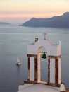 Greek Orthodox Church Bell Tower against Aegean Sea with Sailing Boat at the Sunset, Santorini Royalty Free Stock Photo