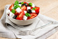 Greek salad in bowl on wooden table with fork Stock Image