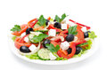Greek salad with feta cheese olives and vegetables isolated on a white background Stock Images