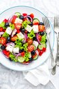 Greek salad of fresh cucumber, tomato, sweet pepper, lettuce, red onion, feta cheese and olives with olive oil Royalty Free Stock Photo