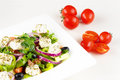 Greek salad with fresh tomato, cucumber, red onion, basil, feta cheese, black olives, Italian herbs and olive oil in white dish on Royalty Free Stock Photo