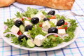 Greek salad with gigantic black olives sheeps cheese bread close up Stock Images