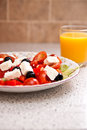 Greek salad with orange juice feta cheese tomatoes and olives a glass of Royalty Free Stock Photo