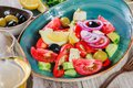 Greek salad of organic vegetables with tomatoes, cucumbers, red onion, olives, feta cheese and glass of wine Royalty Free Stock Photo