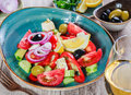Greek salad of organic vegetables with tomatoes, cucumbers, red onion, olives, feta cheese and glass of wine on wooden background Royalty Free Stock Photo