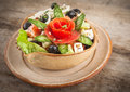 Greek salad in plate on wooden background Royalty Free Stock Photo