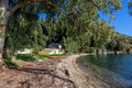Greek seclusion a ruined house shrouded with trees hugs the shore at koloura or kouloura beach on the north eastern shore of corfu Stock Photo