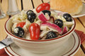 Greek style cole slaw a bowl of with olives tomatoes feta cheese and red onions Stock Image