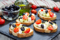 Greek style crostini with feta cheese, tomatoes, cucumber, olives, herbs Royalty Free Stock Photo