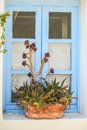 Greek style windows with flowerpot on him Royalty Free Stock Photography