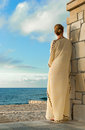 Greek style woman looking for the sea in long silk dress Stock Image