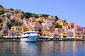 Greek village colorful houses lining the harbor at symi greece Stock Photography