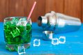 Green alcohol or alcohol free cocktail with straw ice cubes and shaker on a light wooden background Stock Photos
