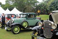Green antique american car in lineup at event ford model a deluxe coupe parked on grass among other old fords showing matching Stock Images