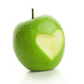 Green apple with cut heart on white Royalty Free Stock Images