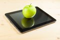 Green apple on digital tablet pc on wood table concept of learn new technology Stock Photography